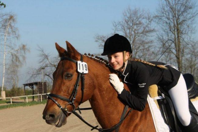 Mädchen sitzt auf einem Pony und umarmt es auf einem Turnier