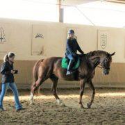 Reitschülerin und Reitlehrerin in einer Reithalle beim Reitunterricht