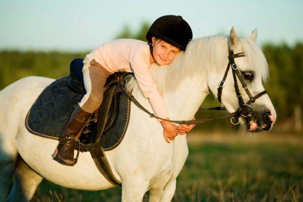 Mädchen sitzt auf einem Pony und umarmt es
